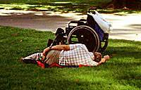 Wheelchair with man laying next to it. Photo copyrighted.