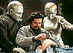 Robot Andrew (Robin Williams) and Robot Galatea (Kiersten Connelly) watch Rupert Burns (Oliver Platt) test his external modifications.